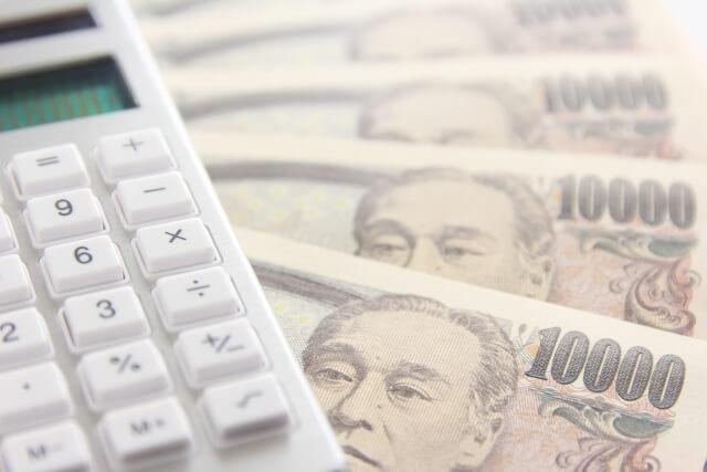 1万円札の上に置かれた電卓