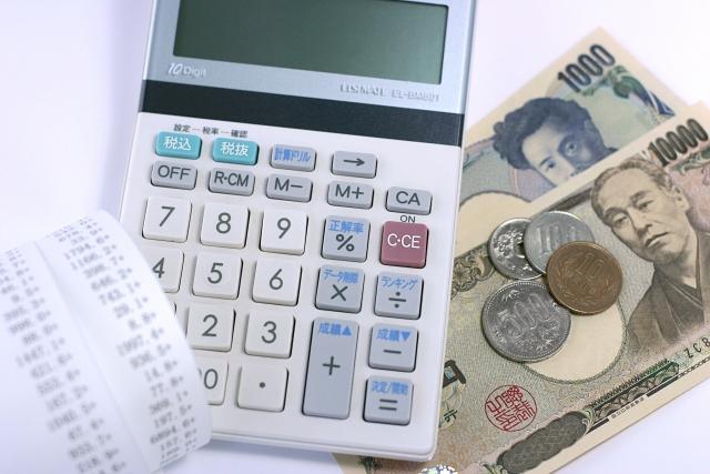 電卓の近くに置かれたお金とレシート