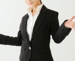 手を広げたスーツの女性